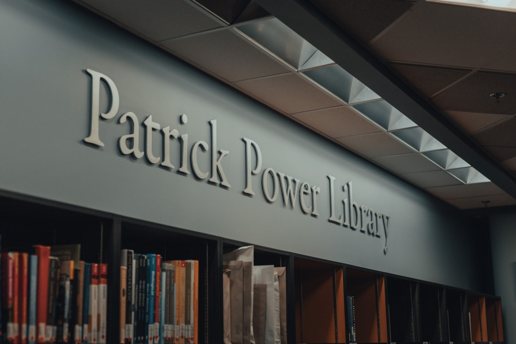 The Patrick Power Library sign at the entrance to the library, with books on shelves underneath.